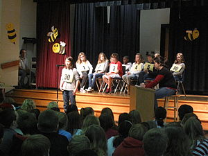 Spelling bee - A spelling bee at an elementary school, with a speller addressing an audience and a judge, with other contestants behind them