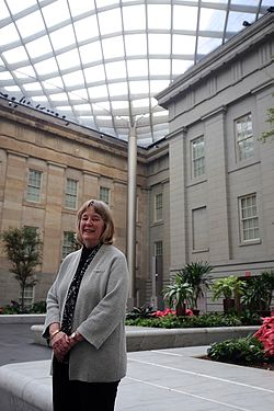 Elizabeth Broun standing in the covered courtyard of the museum
