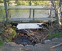A small stream with some downed branches in it flows out of a lake at the rear, underneath a chainlink fence with a small wooden bridge behind it to a concrete culvert in the foreground