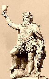 Gambrinus stands holding a chalice aloft, with his right foot atop a beer keg, and a goat to his left.