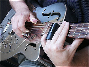 Slide guitar - Example of a bottleneck slide, with fingerpicks and a resonator guitar made of metal.