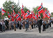 Scouts holding Norwegian flags lead a parade on the 17 May, Norway's Constitution Day
