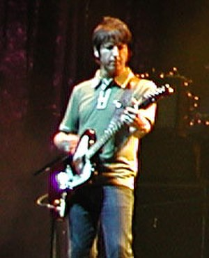 Oasis (band) - Guitarist Gem Archer performing at an Oasis concert.
