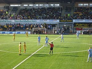 Aspmyra Stadion - Kick-off during a 2008 Norwegian Premier League match between Bodø/Glimt and Lillestrøm. Behind is the old North Stand, and between the stand and the pitch the remains of the all-weather running track