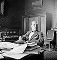 Heer met vlinderstrik zittend achter bureau met rechts van hem een kleine telefo, Bestanddeelnr 255-8800.jpg