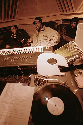 Hip hop production - Hip hop producer and rapper RZA in a music studio with two collaborators. Pictured in the foreground is a synthesizer keyboard and a number of vinyl records; both of these items are key tools that producers and DJs use to create hip hop beats.
