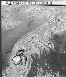 Grayscale image of a well-organized tropical cyclone near the lower-left corner of the image. Although most of the clouds are concentrated towards the lower-left, clouds from the storm extend to the upper-right corner.