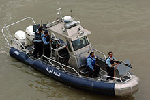 Boat with two motors, a machine gun and four police officers