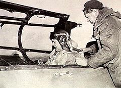 Man in flying helmet putting on a harness in the cockpit of a military aircraft