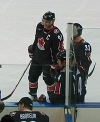 Hockey player in black uniform with a red leaf in the middle. He smiles and stands near the sideline of the rink.