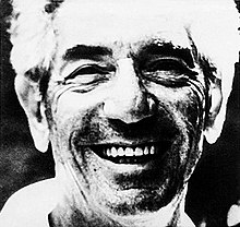 Foto de primer plano en blanco y negro del rostro de un hombre sonriente con cabello claro, cejas oscuras espesas y barba visible.