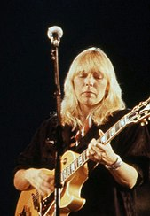 Joni Mitchell, a blond woman, is seen performing on a guitar. She is wearing a black dress and a wristwatch looking downwards.