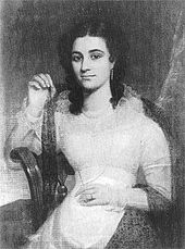 A dark-haired, exotic-looking young lady in a light-coloured dress