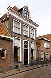 foto van Pand met lijstgevel met voordeur met bovenlicht, geprofileerde lijst met blokjes en dakkapel met top- en zijstukken