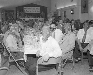 Smog - Highland Park Optimist Club wearing smog-gas masks at banquet, Los Angeles, circa 1954