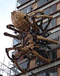 A large mechanical spider on the side of a tall building.
