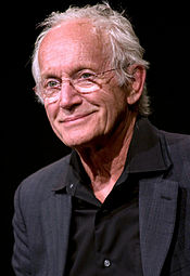 The image is of an older man with glasses wearing a black shirt. He is looking past the camera, smirking.