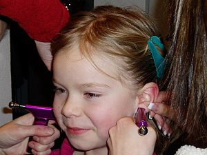 English: A little girl getting her ears pierced.