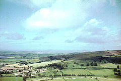 The houses and church of a small village can be seen in the bottom left of the picture. It is surrounded by a patchwork of fields with some trees on a hillside. Large hills in the distance.