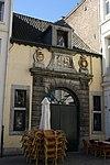 foto van Voormalige wolwaag. Huis met lijstgevel en voorzien van een poort, waarboven zich de wapens bevinden van de bisschop (Jozef Clemens van Beieren) en de staten (Brabant) en een chronogram, 1721.