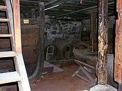 Small dark space, with casks and wooden ladder