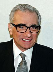 A Caucasian man in his 70s smiling. He is wearing black framed glasses and a tie with a black suit over a white shirt. Behind him is a white background