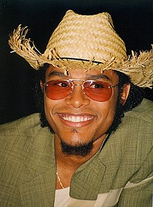 A fair-skinned black man with a straw hat, a green shirt, and ruby sunglasses smiling towards the camera; eyes to the right