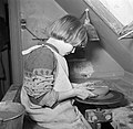 Meisje boetserend met klei op een schopstoel, Bestanddeelnr 252-8956.jpg