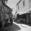 Meisje met een dienblad met broodjes, lopend in een winkelstraat, vermoedelijk i, Bestanddeelnr 255-0375.jpg