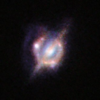 Interacting galaxy - Merging galaxies in the distant Universe through a gravitational magnifying glass.