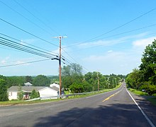 A road in a rural landscape beneath a blue sky, dropping down slightly below the camera and continuing straight for a great distance, with telephone poles and an intersecting road at its left