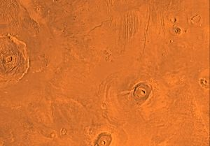 Tharsis quadrangle - Image of the Tharsis Quadrangle (MC-9). The region contains the Olympus Mons, Ascraeus Mons and Pavonis Mons, three of the four largest shield volanoes on Mars. The north-central part contains Ceraunius Fossae.