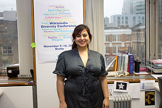 Photo shows Padmini standing in the Wikimedia UK office with a poster behind her
