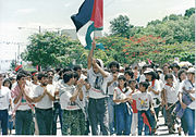 Palestinian Nicaraguans celebrating the 10th anniversary of the Nicaraguan revolution in Managua waving Palestinian and Sandinista flags.