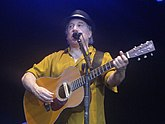 A man behind a microphone holding an acoustic guitar and wearing a yellow shirt and black hat.