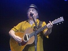 Paul Simon zingt live met een gitaar in de hand.
