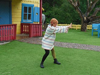 Pippi Longstocking - An actor portrays Pippi in front of a scale model of Villa Villekulla at Astrid Lindgren's World.