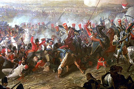 British 10th Hussars of Vivian's Brigade (red shakos - blue uniforms) attacking mixed French troops, including a square of Guard grenadiers (left, middle distance) in the final stages of the battle Plas Newydd (Anglesey) - Waterloo 1.jpg