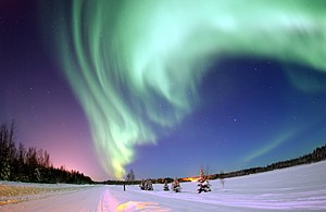 colour photograph of the green aurora borealis over an icy landscape