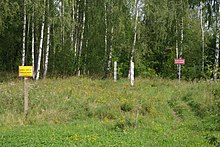 A cleared strip of land in the middle of a wooded area. In the center are two small wooden posts, one painted red and white and the other green and red. On either side are signs in Polish stating that this is the international border and that crossing it here is prohibited