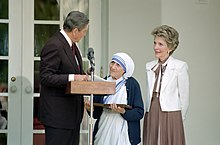 President and Mrs. Ronald Reagan with Mother Teresa, standing at a microphone