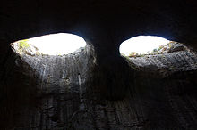 Two eye-like holes in the ceiling of a cave letting light in