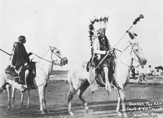 Quanah Parker - Quanah Parker on horseback wearing eagle feather headdress and holding a lance bottom-up.
