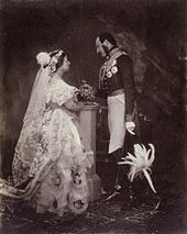 A formal photograph of a beautifully dressed young woman gazing into the eyes of a man who is looking down.