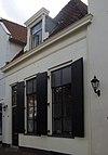 foto van Eenvoudig gepleisterd laag woonhuis met rechte kroonlijst