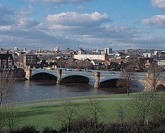 A bridge with three arches spanning a wide river. The near bank is grass with some trees bare of leaves. On the far bank is a cityscape as far as the horizon: few building are distinguishable but in the distance there are steeples and tower blocks. The sky is blue with many white clouds.