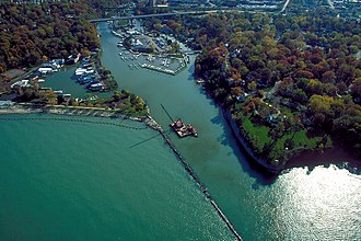 Rocky River (Ohio) - Aerial view, looking southerly, of the river's mouth and surrounding area of discharge into Lake Erie, in Rocky River.  At top, the Clifton Park-West Lake Bridge carries U.S. Route 6 across the river.  At center is a derrick boat operated by the U.S. Army Corps of Engineers, which dredges the navigation channel and maintains the breakwater.