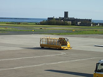 Isle of Man Airport - A baggage loading and transport vehicle drives on the ramp at Ronaldsway Airport.