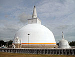 A large white stupa with an orange border near the bottom.