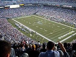 Uno stadio pieno di spettatori, con due squadre di calcio sul campo tra un gioco.
